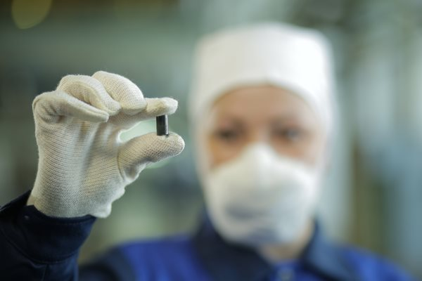 A worked from Kazatomprom holds a uranium pellet between thumb and forefinger