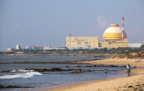 Man walks on beach in front of Kudankulam nuclear power plant, one of India's newest